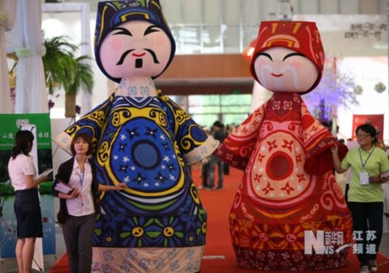8月11日,在南京网友婚博会上,参观者在一家婚庆服务企业的展台咨询。