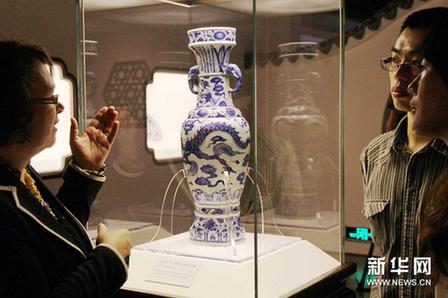 """英国大英博物馆工作人员(左)向参观者介绍珍贵的""""至正十一年铭青花云龙纹象耳瓶""""。新华网图片 许晟摄"""