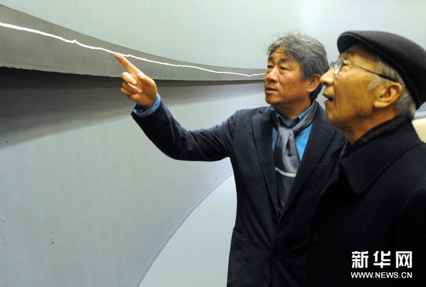 12月7日,谭平(左)在介绍自己的抽象版画作品《+40m》的创作过程。