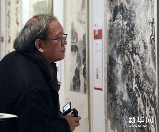 12月8日,参观者在南京艺术学院百年校庆师生美术作品展上欣赏展品