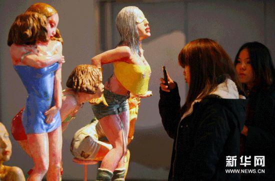 12月8日,参观者在南京艺术学院百年校庆师生美术作品展上欣赏雕塑作品《我是女生》