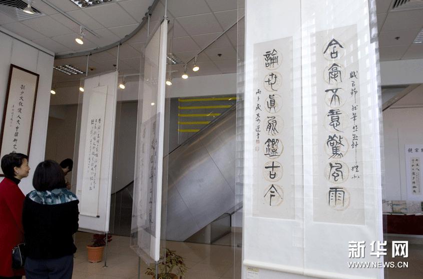 1月21日,两位来宾在香港浸会大学举办的书画展上参观。