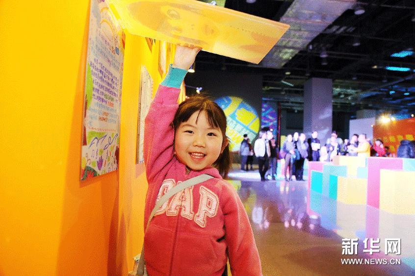 """3月2日,在""""世界儿童融合艺术大展""""上,来自北京的5岁小女孩橙橙展示她所观看的江雪仪小朋友的自画像和自我介绍。"""