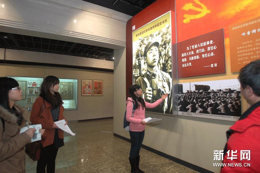 """3月3日,志愿者在""""永远的雷锋""""大型主题展览""""光辉榜样,时代楷模""""展区做准备工作。"""