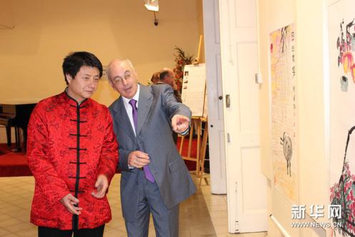 2月28日,在马耳他首都瓦莱塔市,马耳他著名艺术评论家博奇(右)观赏张剑峰作品。新华网图片 赵成 摄