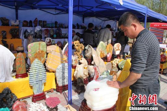 来自山东的参展者马明军在擦拭一块重10公斤的伊朗白玉,售价8000元。朱景朝 摄