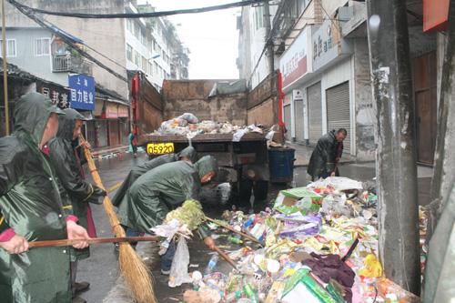 工人清运垃圾,这些垃圾目前送填埋场填埋。