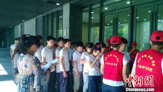 志愿者带领视障孩子参观。 张骏 摄