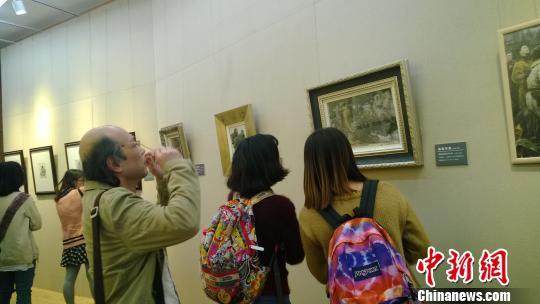 参观者在欣赏画作。 张骏 摄