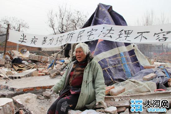 """1月2日上午,平顶山的气温在摄氏零下5度左右,李桂荣老人和几个亲属在已经变成废墟的""""家""""中,费力地找寻自己的东西。"""