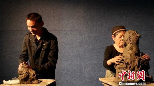"""上海宝山国际民间艺术博览馆举办的""""连接艺术与社会的'盲文'——李秀勤雕塑二十年""""8日揭幕。图为李秀勤与盲人徐马正在互相触摸后互为对方塑头像。 上海宝山国际民间艺术博览馆供稿。 摄"""