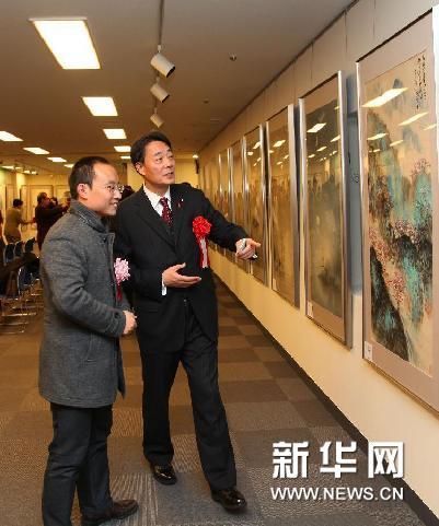 1月20日,在日本东京,日本众议院议员、民主党党首海江田万里(右)在画展上欣赏作品。新华网图片 冯武勇 摄