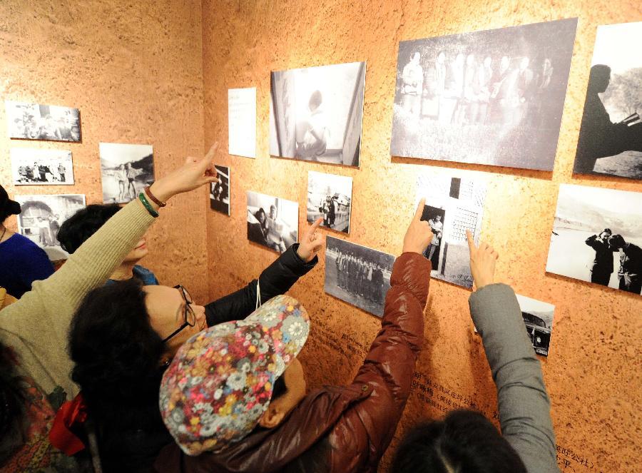 """(1)1月21日,在""""寻根·守望——沐浴圣地洗礼的北京知青""""专题展上,北京老知青们纷纷指出老照片里的自己和战友。"""