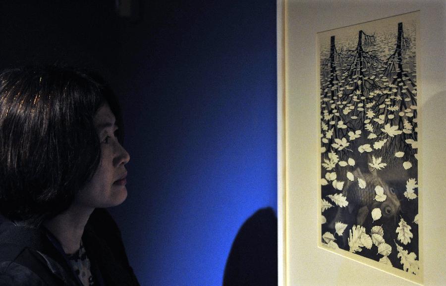 (3)2月26日,一名参观者在台北故宫图书文献大楼欣赏荷兰艺术家艾雪的套色木刻版画《白天与黑夜》。