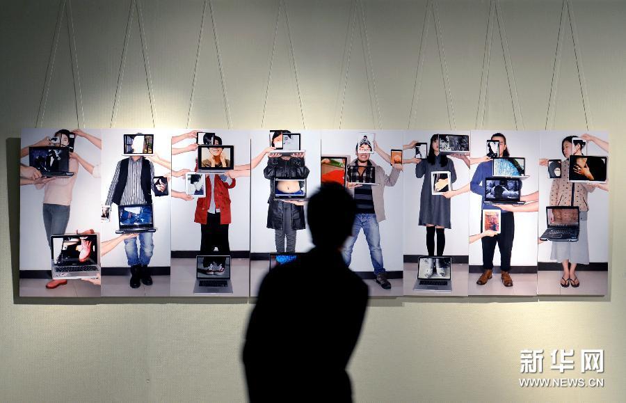 (2)3月10日,参观者在欣赏摄影作品《屏幕嵌肉里了》。