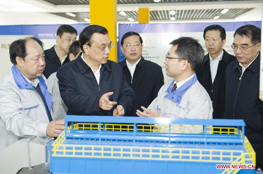 Chinese Premier Li Keqiang (2nd L, front) talks with staff members at a laboratory of Yuanda Science and Technology Innovation Park in Shenyang, capital of northeast China