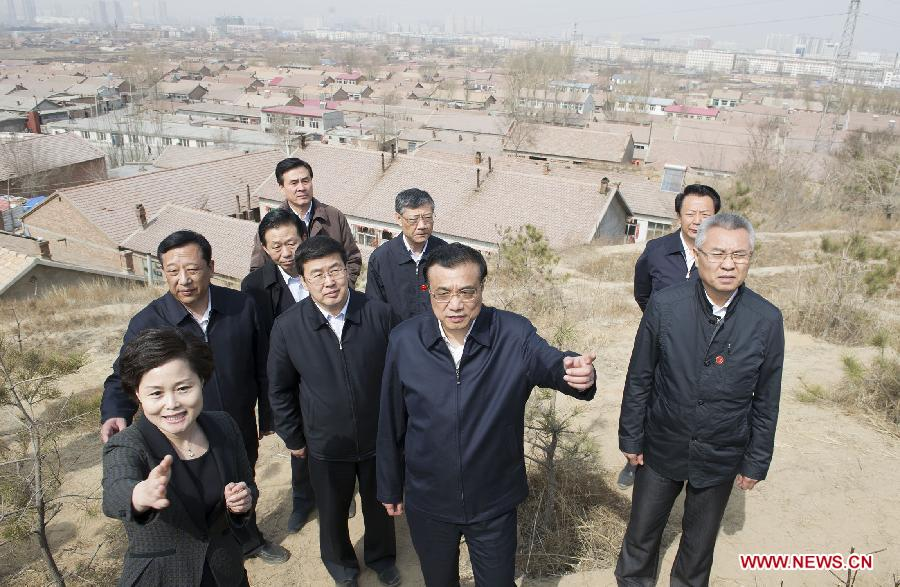 Chinese Premier Li Keqiang (C, front) visits a makeshift home area and learns about the renovation progress, in Chifeng City, north China