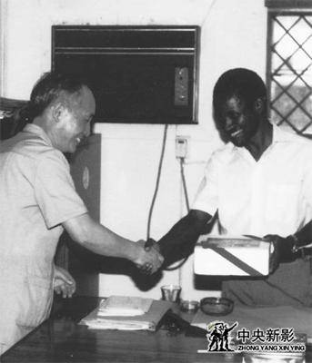 在坦桑尼亚,吴均(左)向坦桑文化局的负责人赠送纪念品