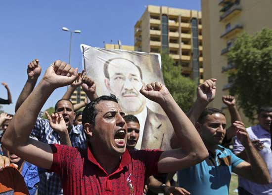 raqis chant pro-government slogans and display placards bearing a picture of embattled Prime Minister Nouri al-Maliki during a demonstration in Baghdad, Iraq, Monday, Aug. 11, 2014.