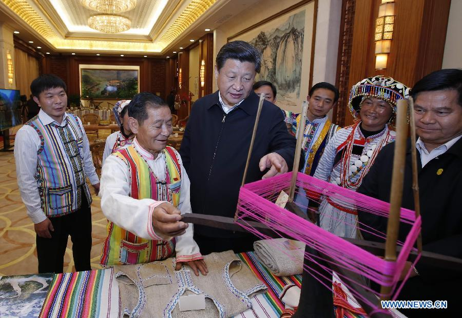 Chinese President Xi Jinping (3rd L) inquires about an instrument to villagers of Dulong ethnic minority group, southwest China