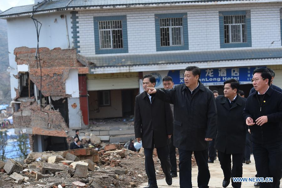 Chinese President Xi Jinping (2nd L front) looks at ruins at Longtoushan Town in Ludian County, which experienced a 6.5 magnitude earthquake in August last year, in southwest China