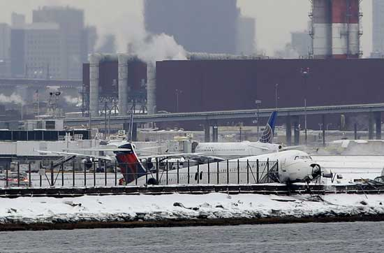 A plane that skidded off the runway at LaGuardia Airport hangs over the edge of the runway in New York, Thursday, March 5, 2015.