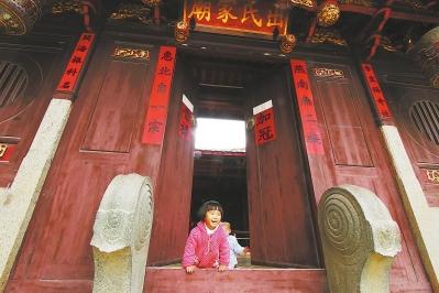 儿童在出氏家庙门口玩耍,家庙的构造整体看上来与当地其他家庙大致相似。