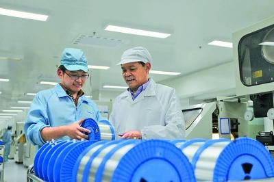 崔根良(右)在生产车间。资料图片