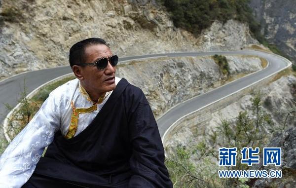 斯那定珠在香格里拉大峡谷内仰望远方(他的一只眼睛近乎失明,经常戴着墨镜),身后是其倾尽所有修建的其中一段公路(5月14日摄)。新华社记者 蔺以光 摄