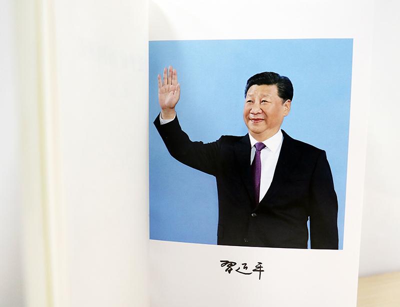 图为《习近平谈治国理政》第二卷扉页后习近平总书记挥手照片,下有总书记个人签名。