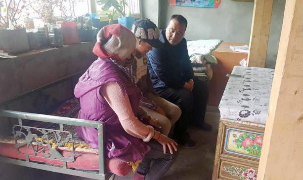 慕育军(右)在结对帮扶的扎囊县藏族群众家里了解情况(摄于2017年1月)。
