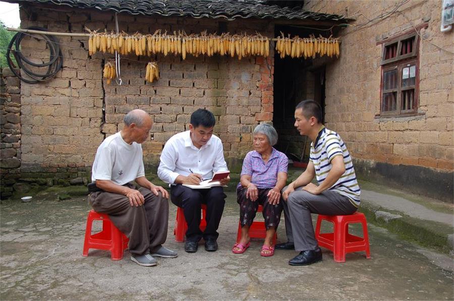 黄树新(左二)在北楼村文聚组贫困户中了解群众获得扶贫补助等情况。(图片来源:广西纪检监察网)