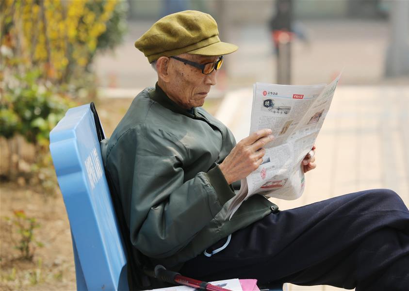 周智夫在干休所小花园中阅读报纸(2015年4月9日摄)。