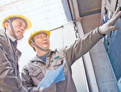 张黎明(右)在认真地开展线路故障检修工作。(资料照片)