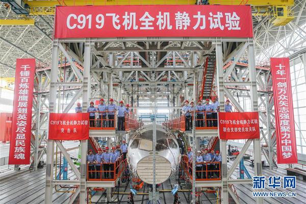 在位于上海浦东机场区域的中国航空工业飞机强度研究所内,工作人员在C919大型客机10001验证飞机的工作平台上合影(6月21日摄)。新华社记者 丁汀 摄