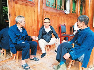 杨平(中)与村民沟通交流。(资料图片)