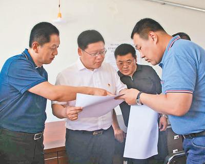 杨勇(左二)在乡镇检查指导脱贫攻坚工作。资料照片
