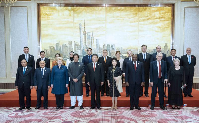 11月4日晚,国家主席习近平和夫人彭丽媛在上海举行宴会,欢迎出席首届中国国际进口博览会的各国贵宾。这是宴会前,习近平和彭丽媛同各国领导人夫妇合影留念。新华社记者 李涛 摄