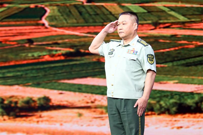 图为印春荣在节目录制现场向观众敬礼