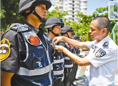 """张兆腾(右)为""""飞鹭支队""""队员整理警容。"""