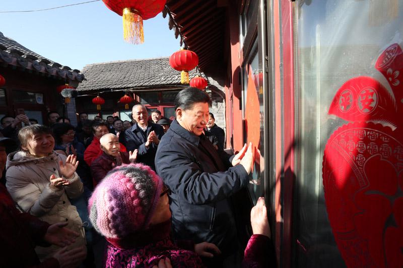 """2月1日,中共中央总书记、国家主席、中央军委主席习近平在北京看望慰问基层干部群众,考察北京冬奥会、冬残奥会筹办工作。这是1日上午,习近平在前门东区草厂四条胡同32号院,高兴地拿起一幅""""福""""字,亲自贴到门上,给这里的老街坊们拜年。新华社记者 鞠鹏 摄"""