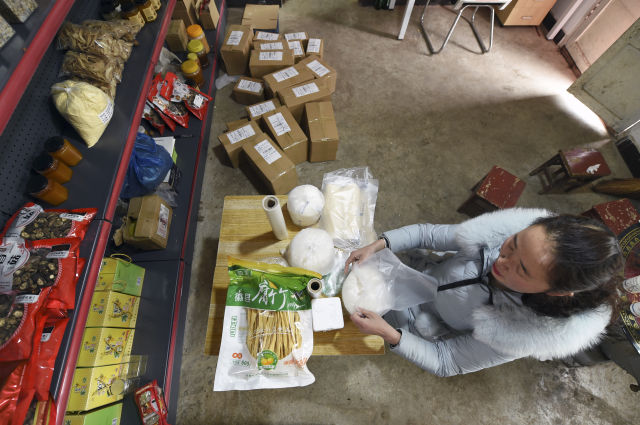 """2月19日,在位于甘肃省陇南市徽县水阳镇石滩村的家中,梁倩娟为买家打包货物。她开办""""陇上庄园""""网店,将当地出产的农产品通过网络销售,带动了乡亲们脱贫增收。"""
