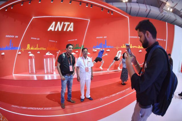 在一年一度的中国(晋江)国际鞋业暨国际体育产业博览会上,来自印度的客商在安踏展位前留影(2018年4月19日摄)。