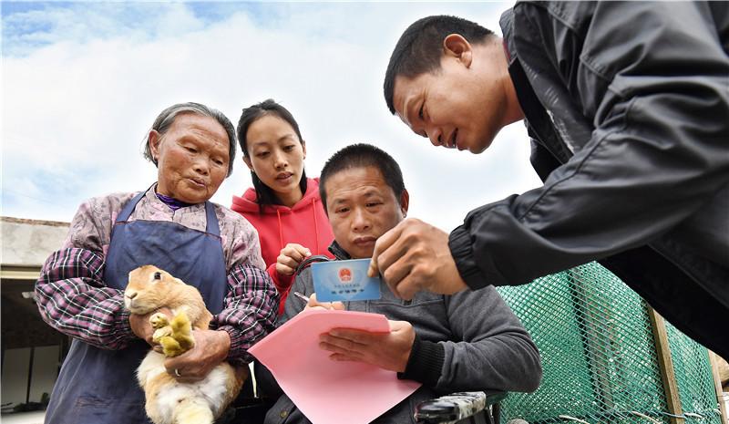 在上杭县才溪镇溪北村,残疾人贫困户刘喜明高兴地领到扶贫款。在镇、村干部的结对帮扶下,刘喜明通过发展养殖肉兔实现脱贫,并搬进了新居。