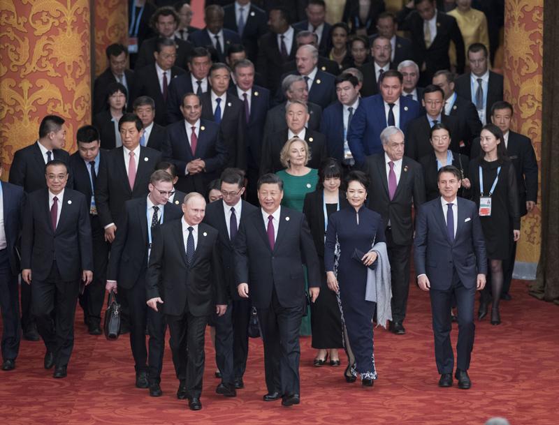 """4月26日,国家主席习近平和夫人彭丽媛在北京人民大会堂举行宴会,欢迎出席第二届""""一带一路""""国际合作高峰论坛的外方领导人夫妇及嘉宾。这是习近平和彭丽媛同贵宾们一同步入宴会厅。"""