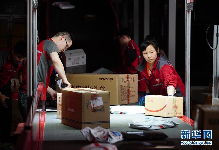 工人在位于西安的京东智能物流中心细分区龙门架下整理包裹(6月3日摄)。龙门架扫描后,包裹的出库物流信息将自动更新。