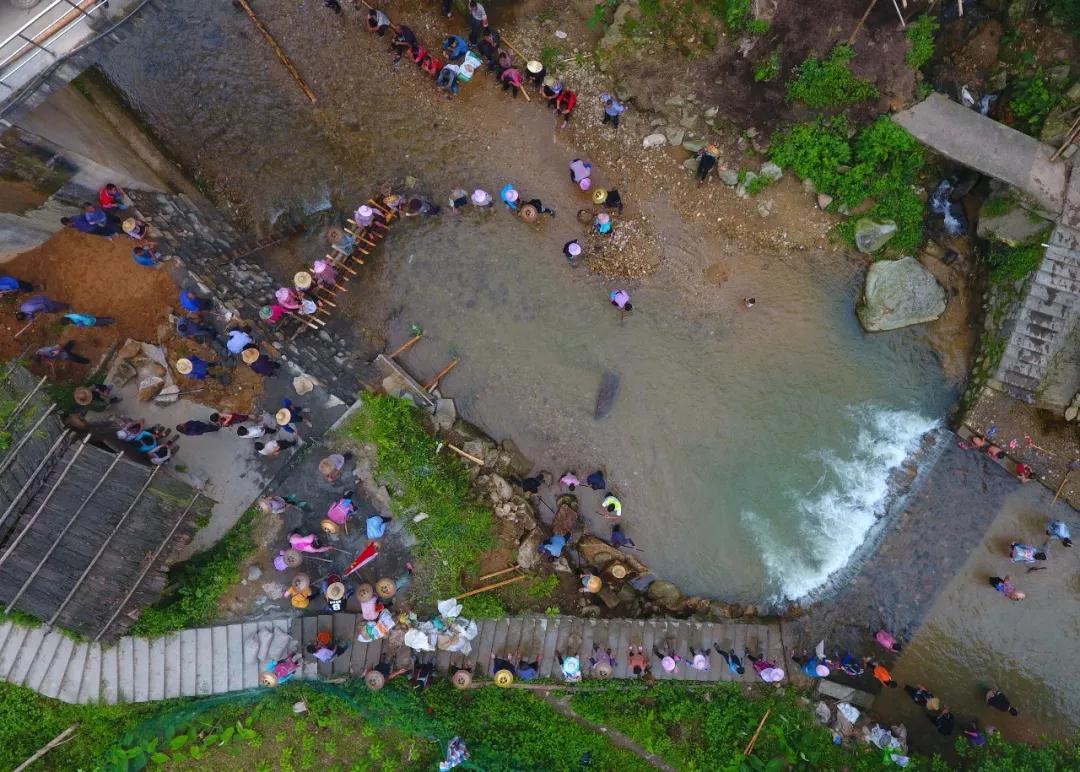 在黔桂交界的乌英苗寨,驻村扶贫干部和村民在修河堤(7月3日无人机拍摄)。
