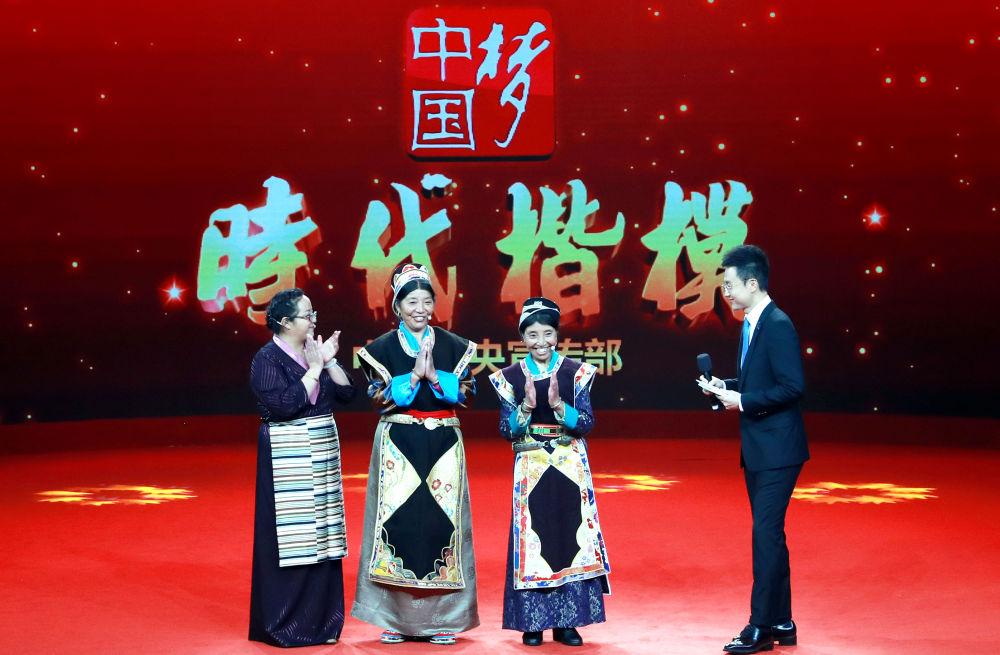 """被授予""""时代楷模""""称号的卓嘎(右二)、央宗(左二)姐妹在""""时代楷模""""授予仪式上与主持人和观众互动交流(2018年10月16日摄)。新华社记者 潘旭 摄"""