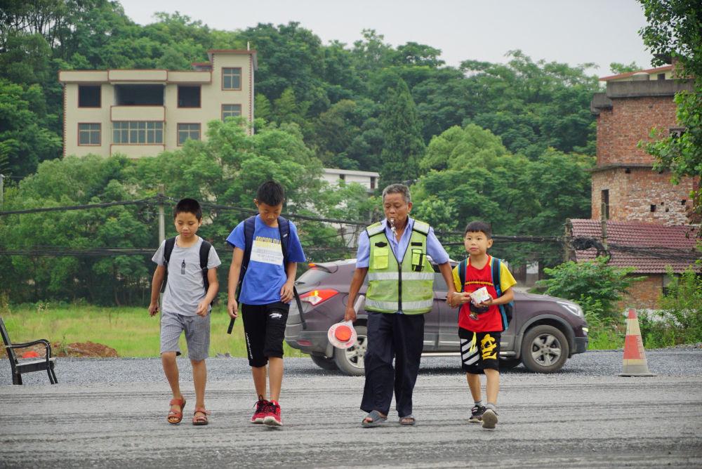 江西省上栗县彭高镇东山村的李丙味(右二)带领孩子们过马路(5月30日摄)。新华社记者 周密 摄