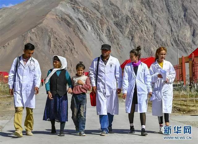 新疆塔什库尔干塔吉克自治县达布达尔乡热斯喀木村村医发尔亚特·塔西白克(右三)与医务人员来到当地易地扶贫搬迁安置点出诊(2019年7月7日摄)。随着医疗扶贫的推进,新疆牧区的医疗条件和水平大幅提升,牧民享受到越来越多、越来越便利的医疗惠民服务。新华社记者 胡虎虎 摄